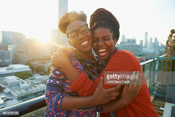 women hugging on city rooftop - sister stock pictures, royalty-free photos & images