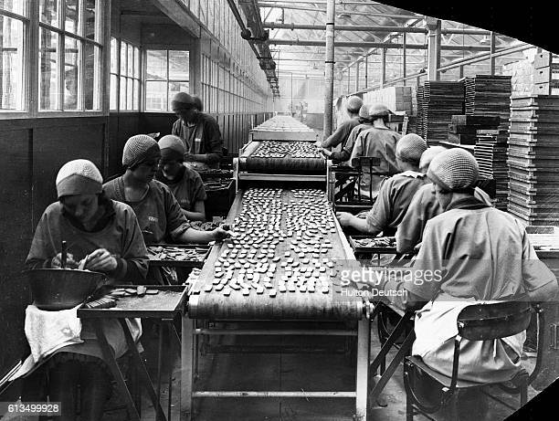 Women icing biscuits in a factory in Liverpool, England in 1926. Biscuits being coated with coloured sugar icing. Scenes at the biscuit factory of W....