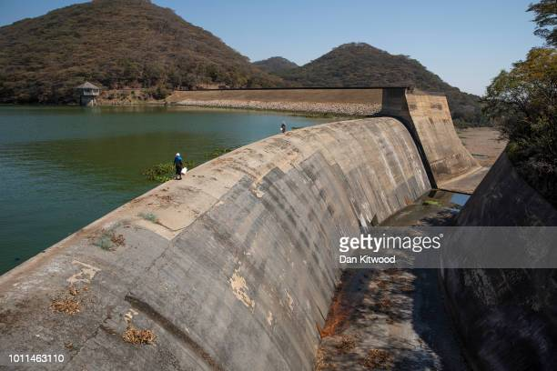 Women illegally fishing walk along the dam wall at Lake Chivero on August 5 2018 in Harare Zimbabwe Lake Chivero is 32km South West of Zimbabwe's...