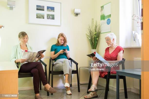 women in a clinic waiting room - doctor's surgery stock pictures, royalty-free photos & images
