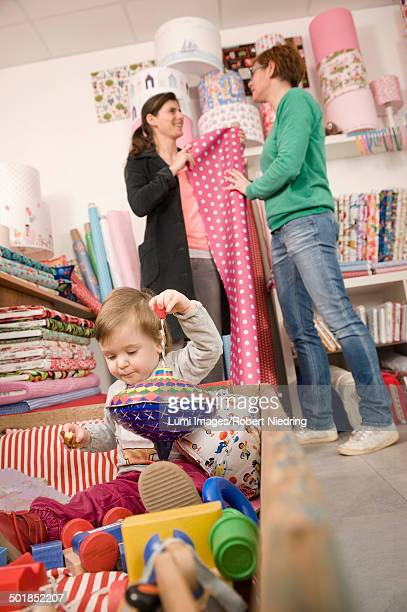Women In A Shop, Baby Girl Playing in Foreground, Munich, Bavaria, Germany, Europe
