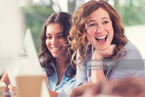 Zwei Frauen in einem Büro lachen.