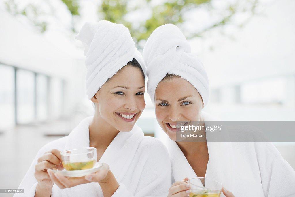 Women in bathrobes drinking tea at spa : Stock Photo