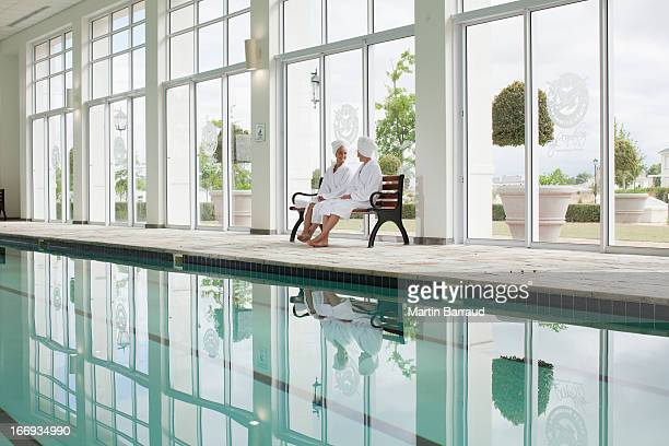 women in bathrobes sitting on bench poolside at spa - health farm stock pictures, royalty-free photos & images