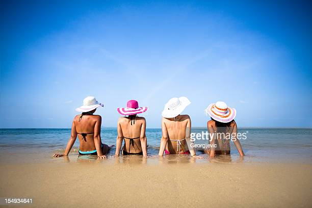 women in beach - women sunbathing stock photos and pictures