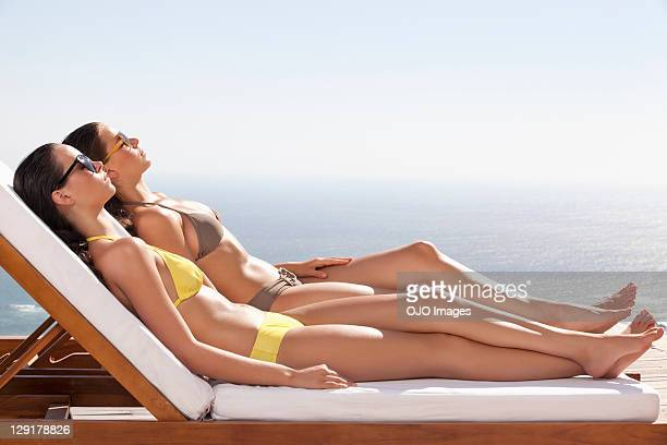women in bikini resting on lounge chair - girls sunbathing stock photos and pictures