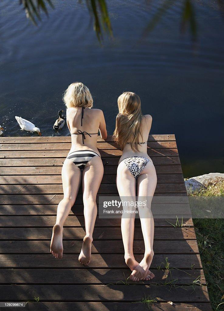 Women in bikinis laying on deck : Stock Photo