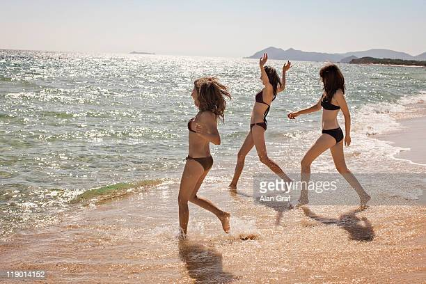 Women in bikinis playing in surf