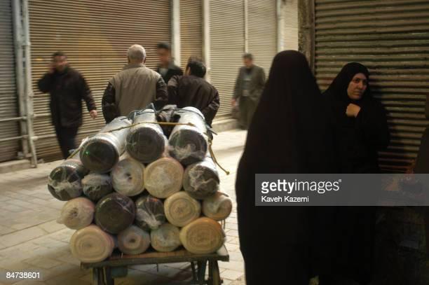 Women in black chadors stand at a corner in Tehran's grand bazaar, 28th February 2004.