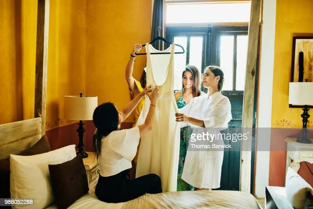 Women in bridal party admiring wedding dress with bride in hotel room before ceremony