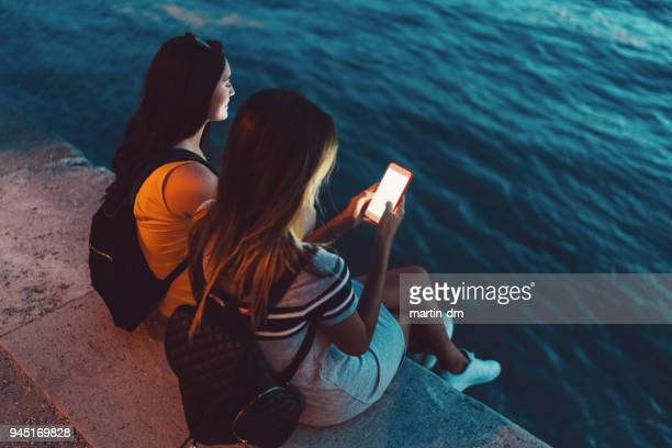 women in budapest texting at danube riverbank - riverbank stock photos and pictures