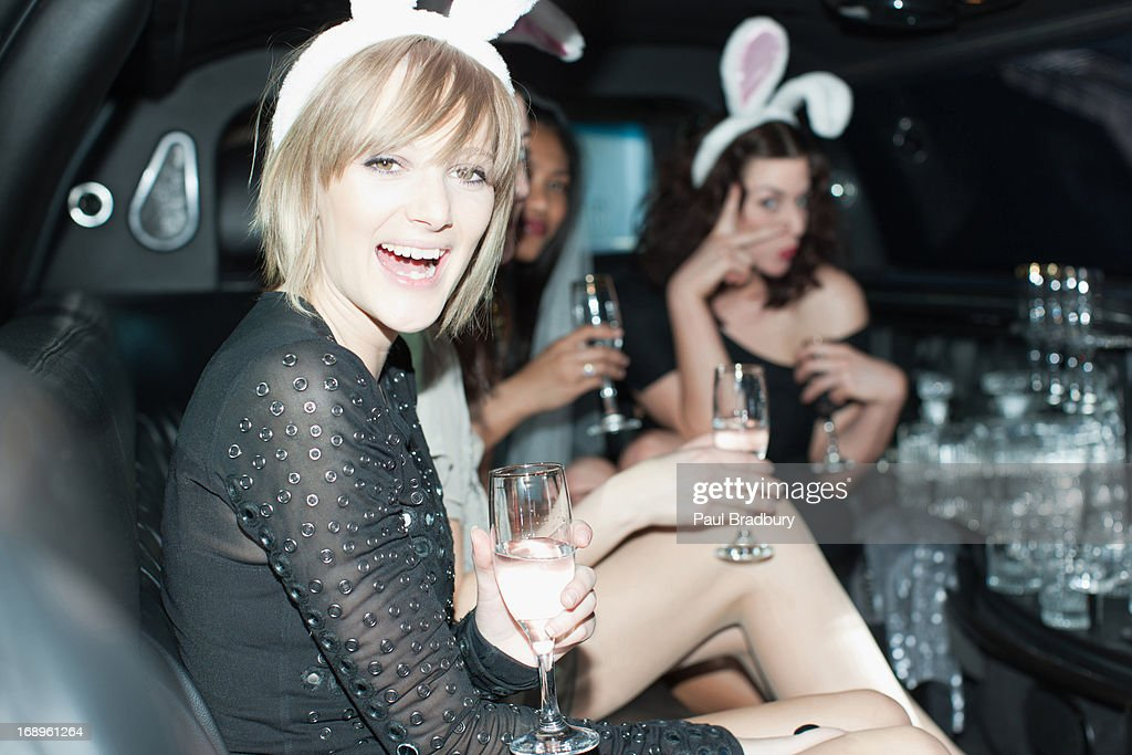 Women in bunny ears having champagne in back of limo : Stock Photo
