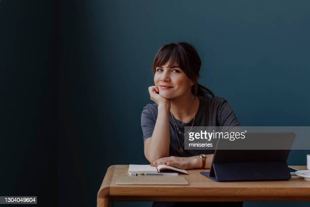 women in business: a smiling young businesswoman using a digital tablet at her office - attending stock pictures, royalty-free photos & images