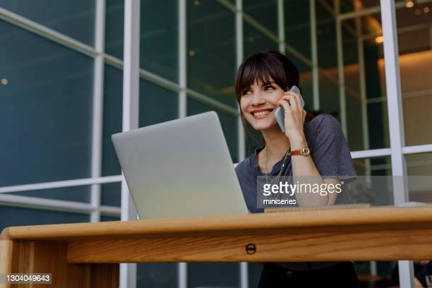 women in business: a smiling young businesswoman using a laptop at her office - attending stock pictures, royalty-free photos & images