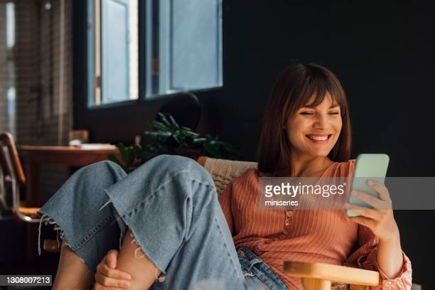 women in business: beautiful smiling young businesswoman using a mobile phone while sitting casually in a chair - pink blouse stock pictures, royalty-free photos & images