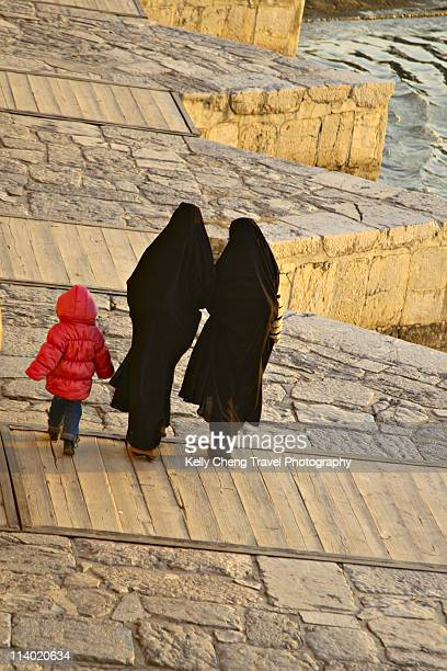 Women in chador and girl in pink