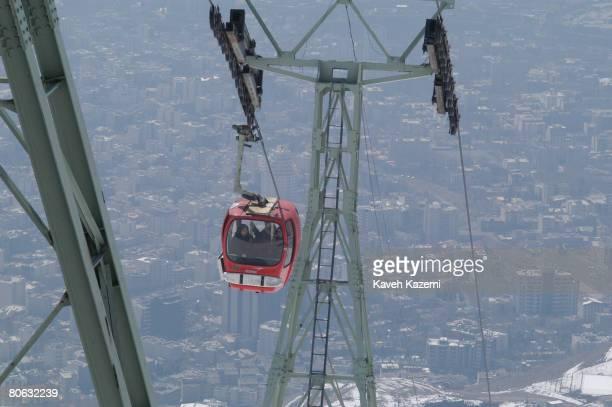 Women in chador ascend the Tochal cablecar in north Tehran, while the city spreads out beneath them, 22nd March 2004.