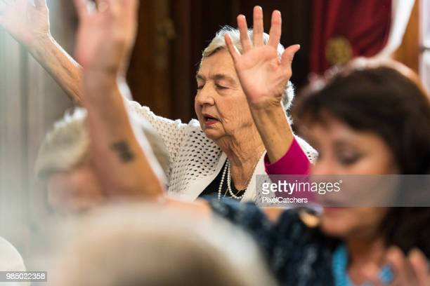 Women in church singing together with arms raised