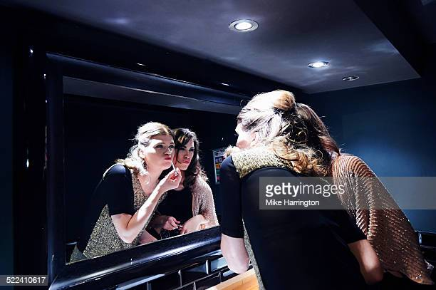 Women in club toilets applying lipgloss in mirror.