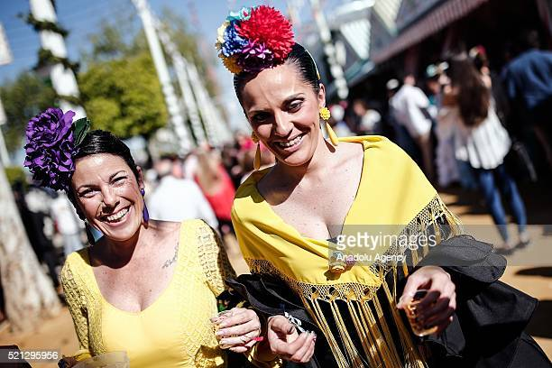 Women in colorful flamenco dresses at the 'Feria de Abril 2016' the traditional Seville's Fair with 169 years of history on April 14 Seville Spain...