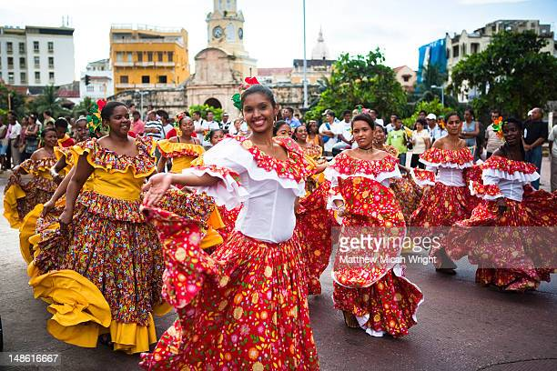 Women in colourful dresses in University parade through the streets of Getsemani