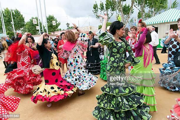 Women in colourful flamenco dresses dancing at the Seville April Fair or the Feria de abril de Sevilla