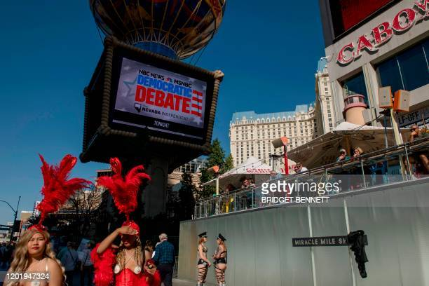 Women in costume are seen below a screen advertising the Democratic Presidential Debate hosted by NBC News and MSNBC with The Nevada Independent on...