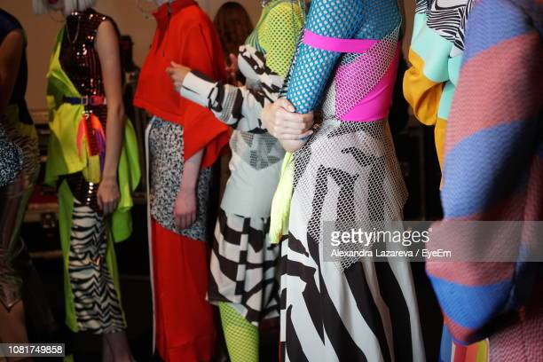 women in costumes standing in room during event - modenschau stock-fotos und bilder
