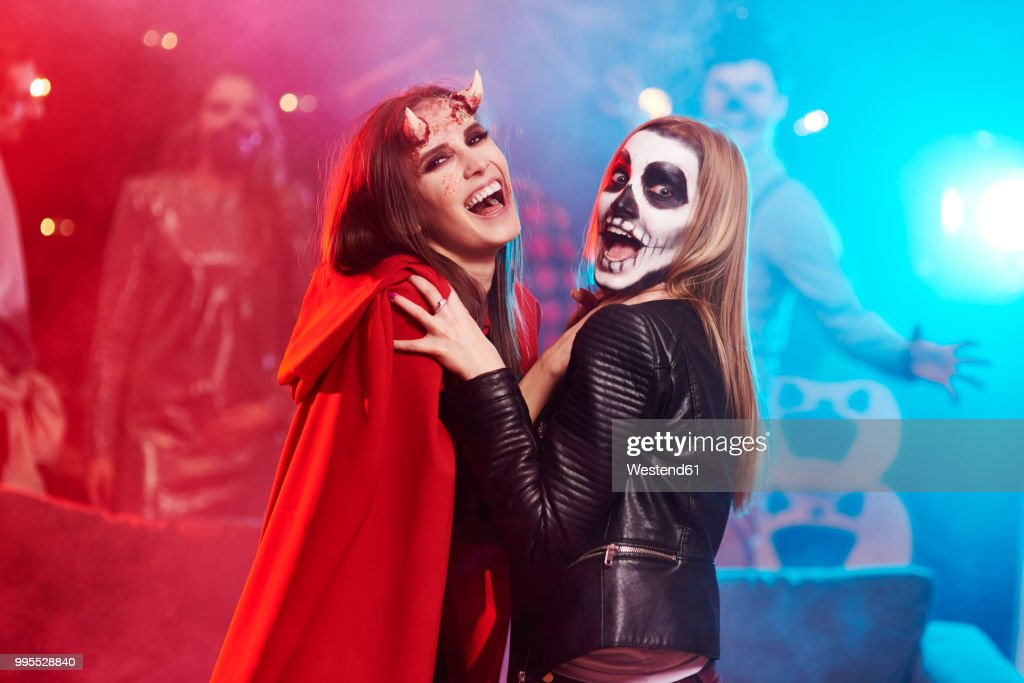 Women in creepy costumes dancing at Halloween party : Stock Photo