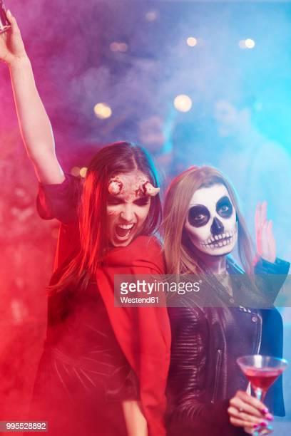 women in creepy costumes dancing at halloween party - 扮装 ストックフォトと画像