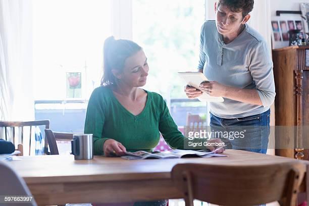 women in dining room sitting at table reading magazine - sigrid gombert stock-fotos und bilder