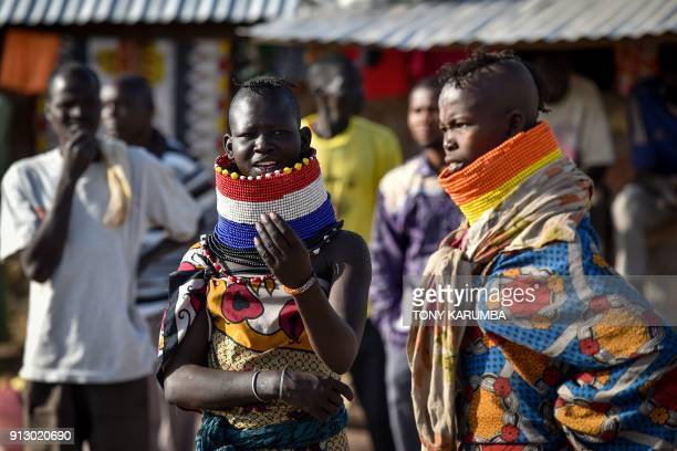 Women in elaborate neck adornements from the local Turkana community look on at Kalobeyei refugee settlement scheme in Kakuma a collaborative effort...