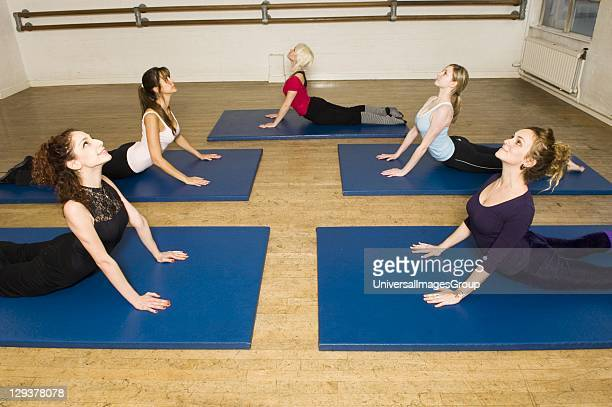 Women in exercise class practicing Pilates cobra position An exercise class at the Body Control Centre in London practice the Pilates Cobra position...
