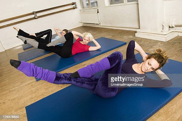 Women in exercise class practicing Pilates criss cross position Pilates is the physical fitness system developed in the early 20th century by Joseph...