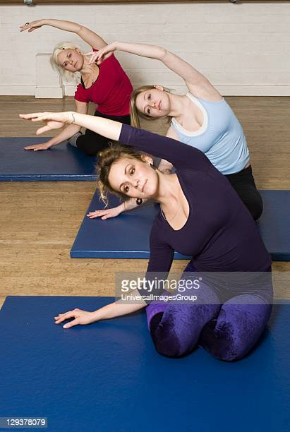 Women in exercise class practicing Pilates mermaid position An exercise class at the Body Control Centre in London practice the Pilates Mermaid...