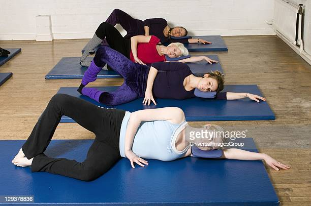 Women in exercise class practicing Pilates oyster position An exercise class at the Body Control Centre in London practice the Pilates Oyster...