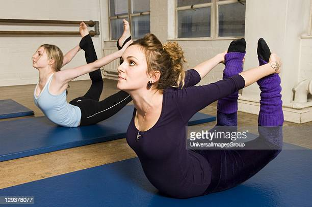 Women in exercise class practicing Pilates rocker position An exercise class at the Body Control Centre in London practice a Pilates Rocker position...