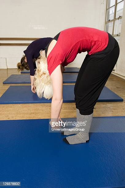 Women in exercise class practicing Pilates roll down position An exercise class at the Body Control Centre in London practice a Pilates Roll Down...
