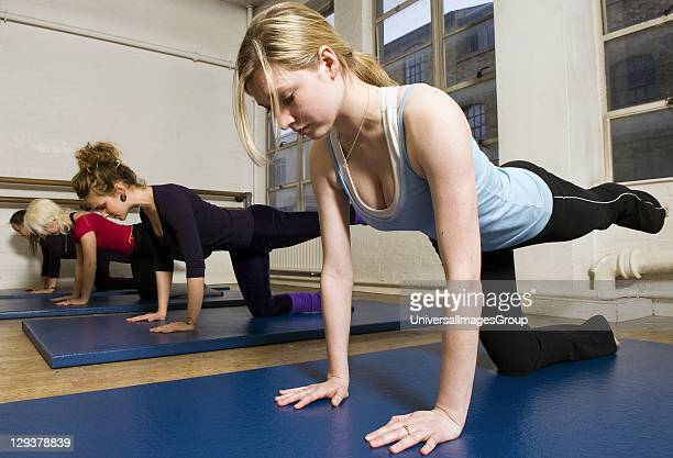 Women in exercise class practicing Pilates table legs routine An exercise class at the Body Control Centre in London in a Pilates Table Legs routine...