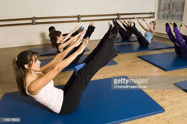Women in exercise class practicing Pilates teaser position An exercise class at the Body Control Centre in London practice a Pilates Teaser position...
