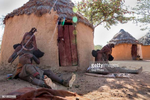 women in front of the huts in himba village - himba foto e immagini stock