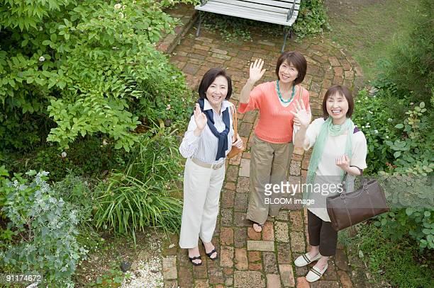women in garden, smiling, view from above - 手を振る ストックフォトと画像