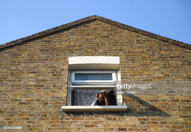 A women in Hackney looks out of her window on April 11 2020 in London England The Coronavirus pandemic has spread to many countries across the world...