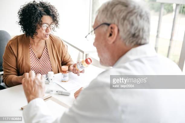 women in her 50 attended by family doctor - menopause stock pictures, royalty-free photos & images