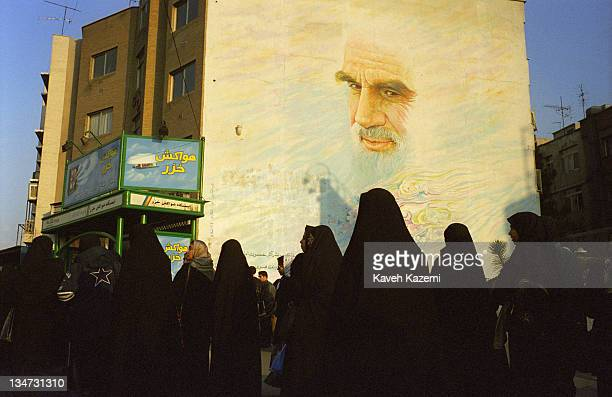 Women in Islamic dress wait for a bus in a segregated queue in Vanak Square, Tehran, circa 2001. Above them is a large mural portrait of Ayatollah...