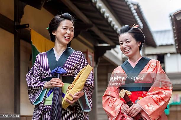 women in kimono under umbrellas talk on the street, japan - alleen japans stockfoto's en -beelden
