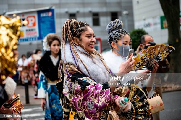 """Women in kimonos take pictures during """"Coming-of-Age Day"""" celebrations in Yokohama on January 11, 2021 under a state of emergency over the Covid-19..."""