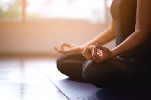 Women in meditation while practicing yoga in a training room. Happy, calm and relaxing. 1166417394
