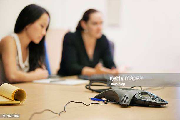 Women in meeting with telephone conference call speaker in foreground
