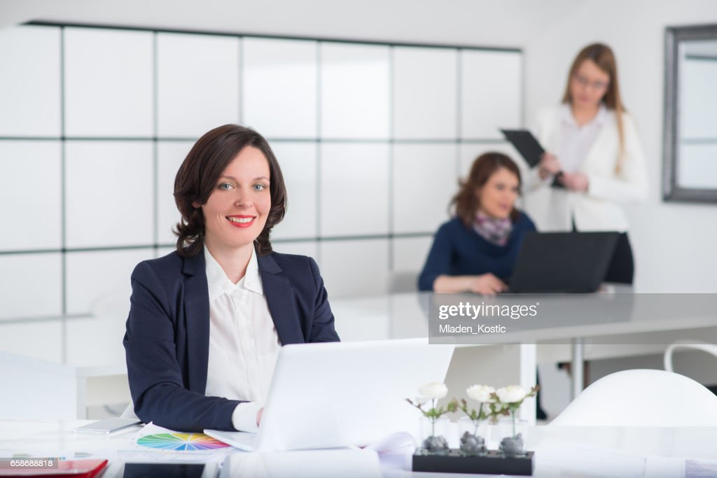 Women In Office Working On Laptop Busy Work Day Stock Photo